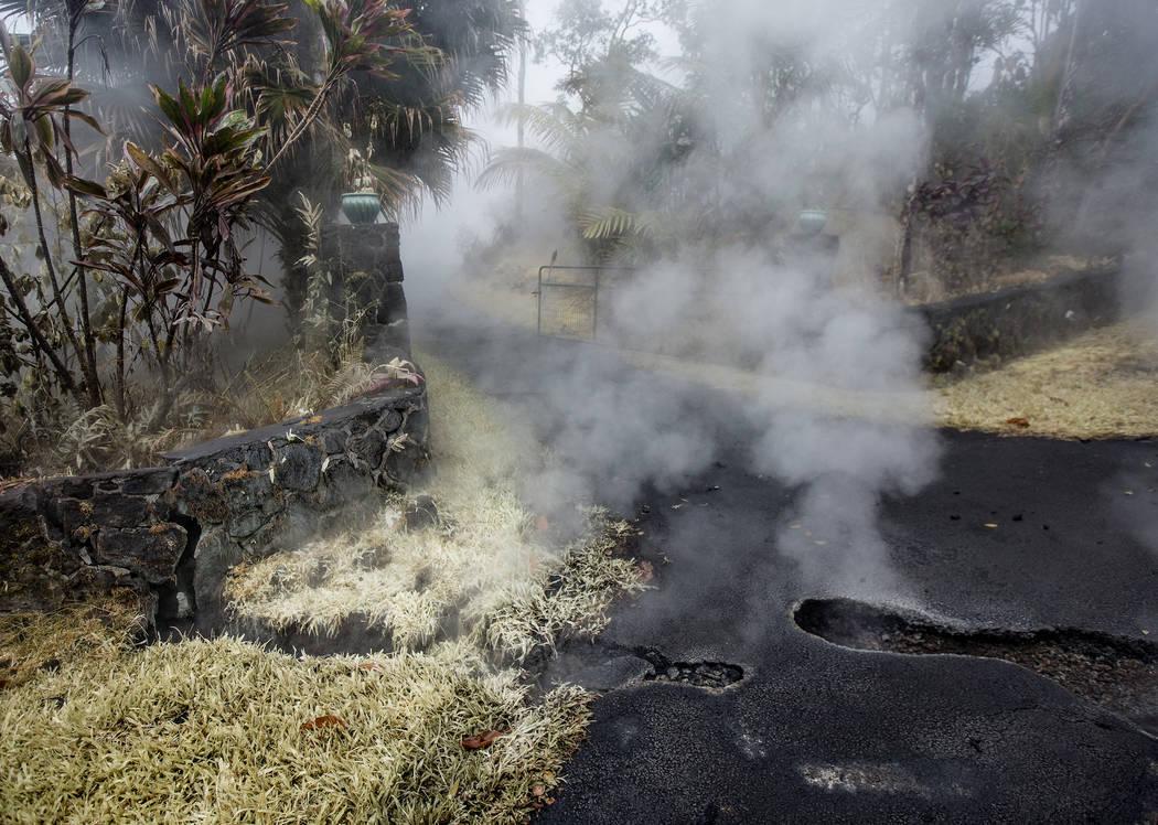 El vapor y el azufre salen de las grietas en la calle Moku, a la entrada de un camino de entrada en Leilani Estates, el martes 8 de mayo de 2018, en Pahoa, Hawaii. La policía ha ido de puerta en ...