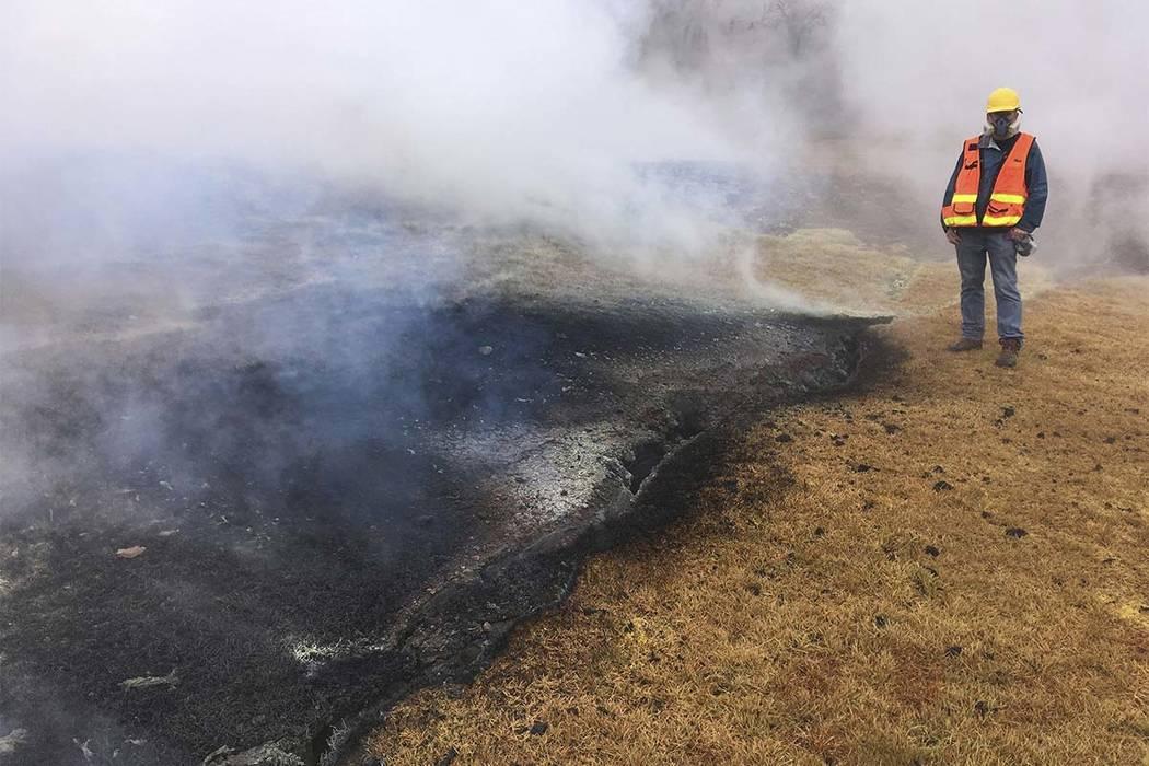 En este martes, 8 de mayo de 2018, foto del Servicio Geológico de los EE.UU., Un geólogo examina una parte de la fisura inactiva 10 en la subdivisión de Leilani Estates, cerca de Pahoa en la is ...