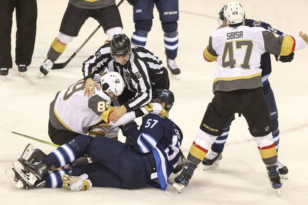 Un oficial rompe una pelea entre el ala derecha de Vegas Golden Knights: Alex Tuch (89) y el defensor de Winnipeg Jets: Tyler Myers (57) durante el segundo período en el Juego 1 de una serie de p ...