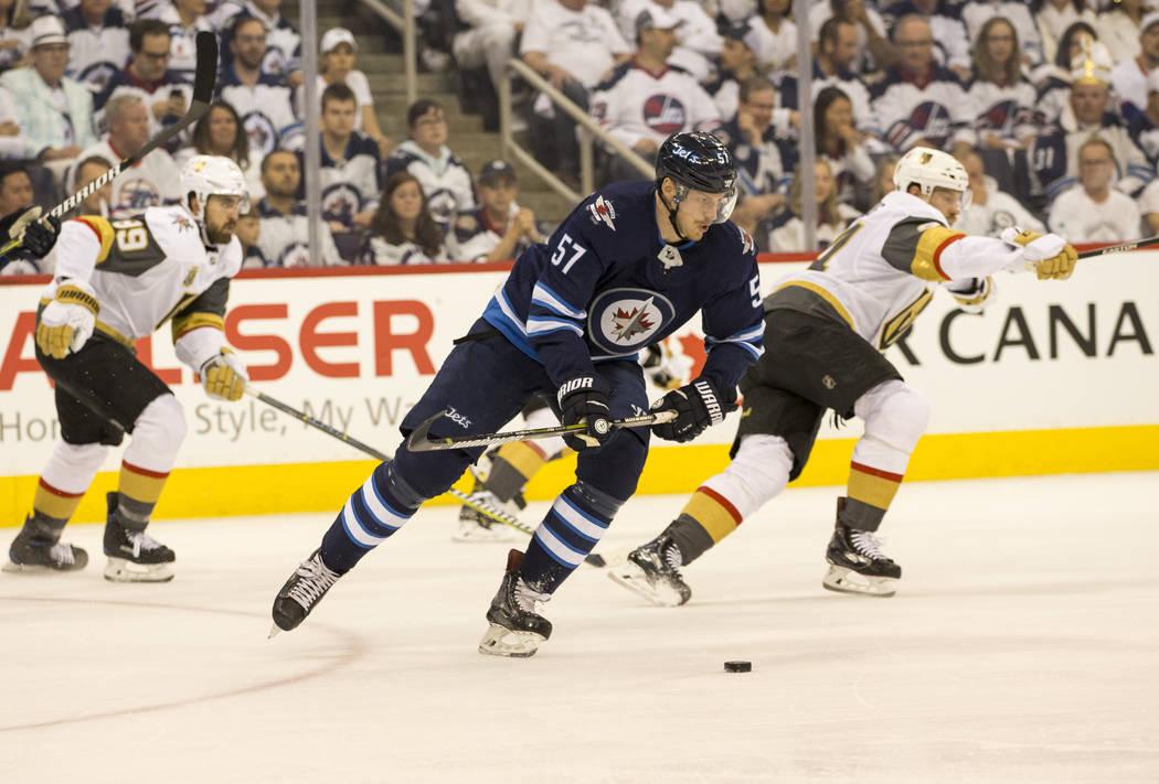 El defensor de Winnipeg Jets: Tyler Myers (57), controla el disco contra Vegas Golden Knights durante el primer período en el Juego 1 de una serie de playoffs de tercera ronda de hockey de la NHL ...