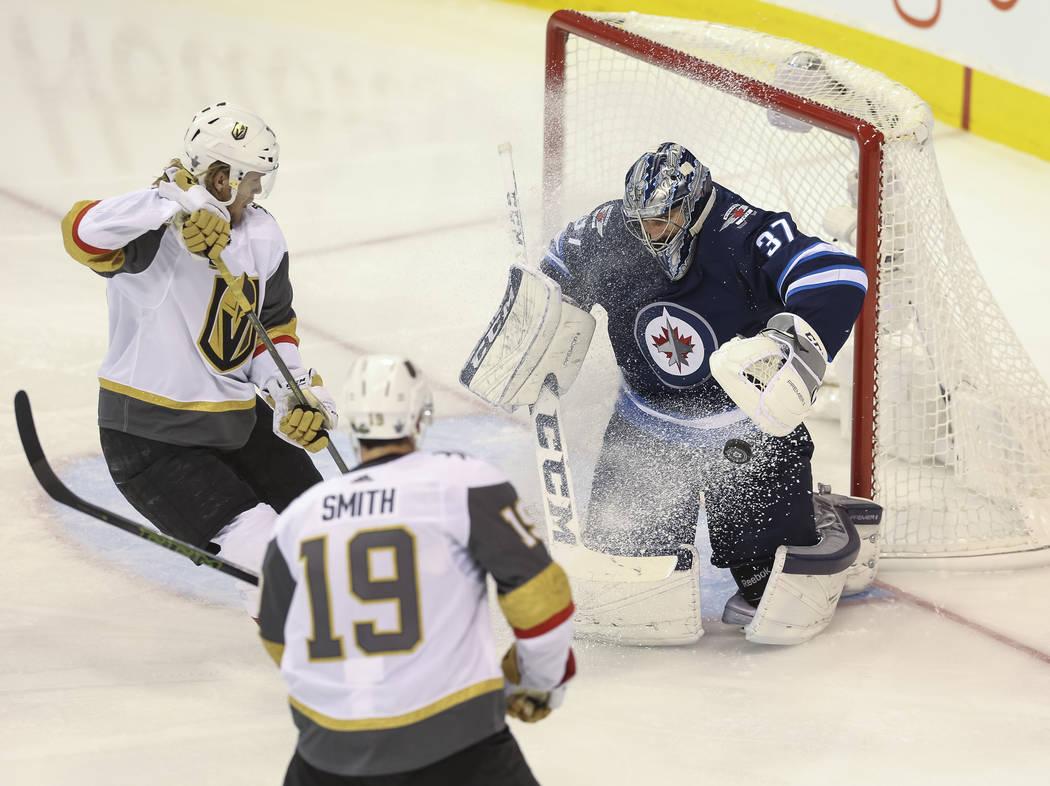 El portero de Winnipeg Jets: Connor Hellebuyck (37) desvía un intento del centro de Vegas Golden Knights: William Karlsson (71), mientras el ala derecha de los Caballeros: Reilly Smith (19), obse ...