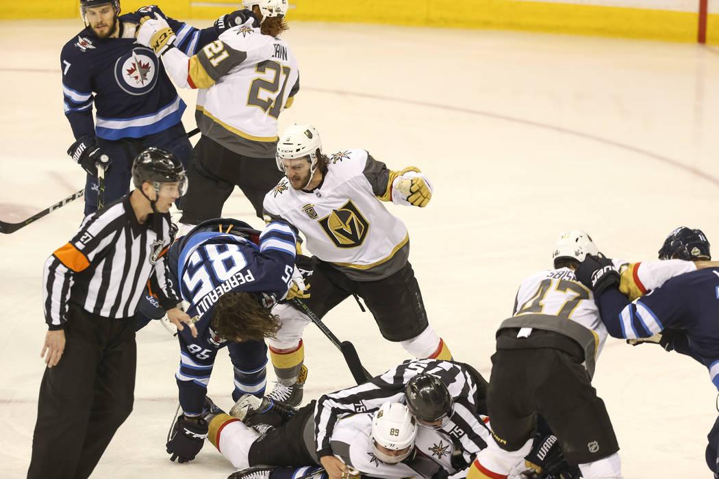 Los jugadores de Vegas Golden Knights y Winnipeg Jets luchan durante el segundo período en el Juego 1 de una serie de playoffs de tercera ronda de hockey de la NHL en el Bell MTS Place en Winnipe ...