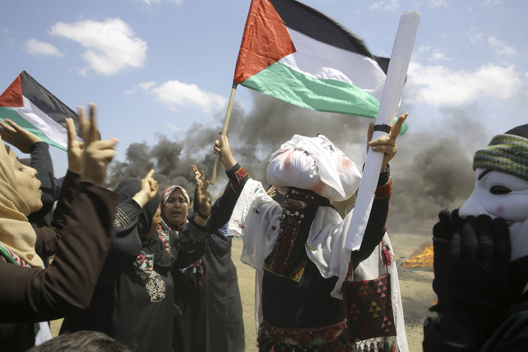 Mujeres palestinas agitan banderas nacionales y entonan consignas cerca de la valla fronteriza israelí, al este de Khan Younis, en la frontera de Gaza, el lunes 14 de mayo de 2018. Miles de pales ...