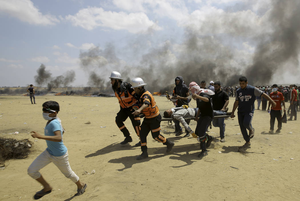 Médicos y manifestantes palestinos evacuan a un joven herido durante una protesta en la frontera de Gaza con Israel, al este de Khan Younis, Gaza, el lunes 14 de mayo de 2018. Miles de palestinos ...