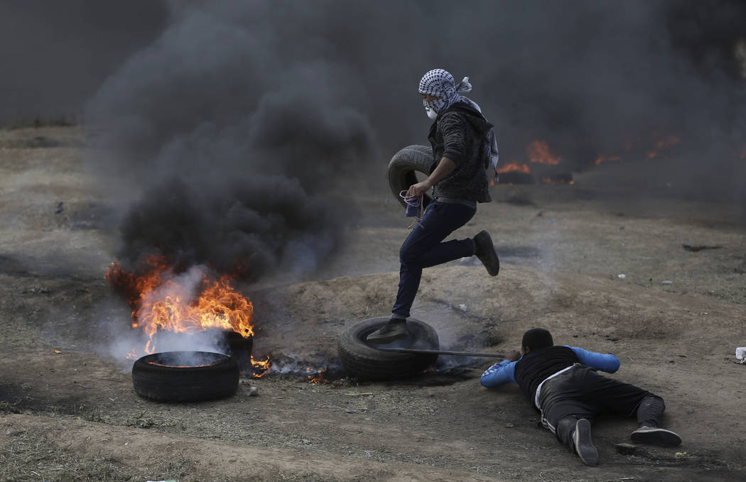 Los manifestantes palestinos queman neumáticos durante una protesta en la frontera de Gaza con Israel, el lunes 14 de mayo de 2018. Miles de palestinos protestan cerca de la frontera de Gaza con ...