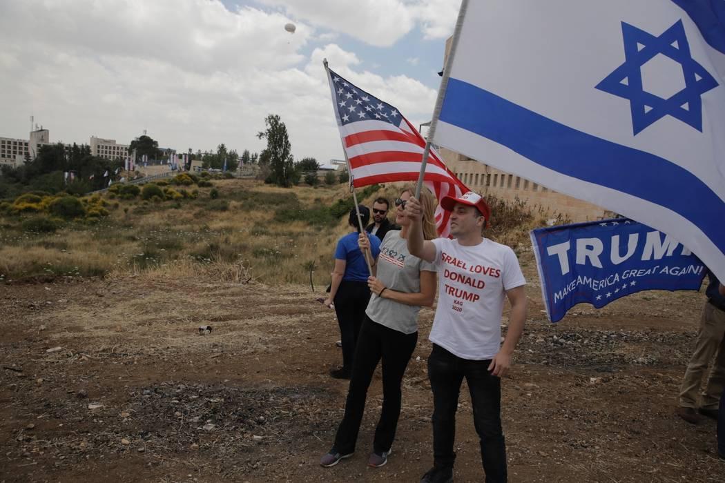 Los israelíes sostienen banderas estadounidenses e israelíes con la nueva embajada de EE.UU. En el fondo en Jerusalén, el lunes 14 de mayo de 2018. Israel se preparó para la inauguración fest ...