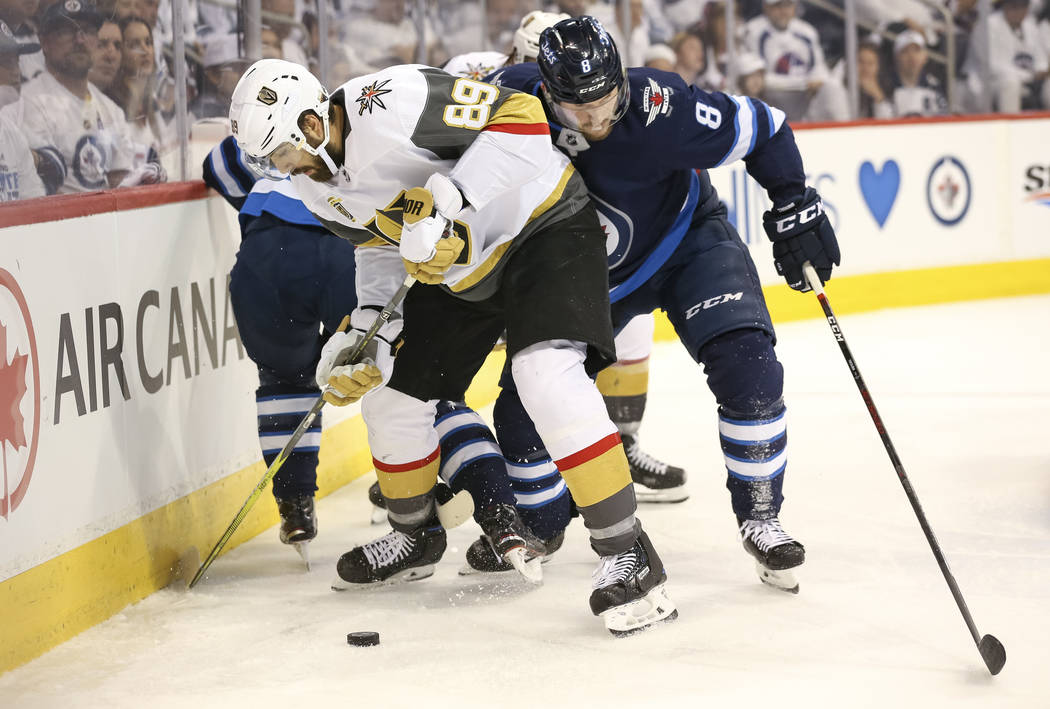 El alero derecho de Vegas Golden Knights: Alex Tuch (89), mantiene el disco alejado del defensor de los Jets de Winnipeg: Jacob Trouba (8) durante el segundo período en el Juego 2 de una serie de ...