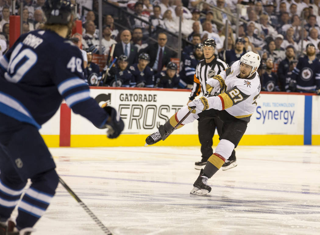 El defensor de Vegas Golden Knights: Shea Theodore (27) lanza un tiro a puerta contra los Winnipeg Jets durante el segundo período en el Juego 2 de una serie de playoffs de la NHL en la tercera r ...