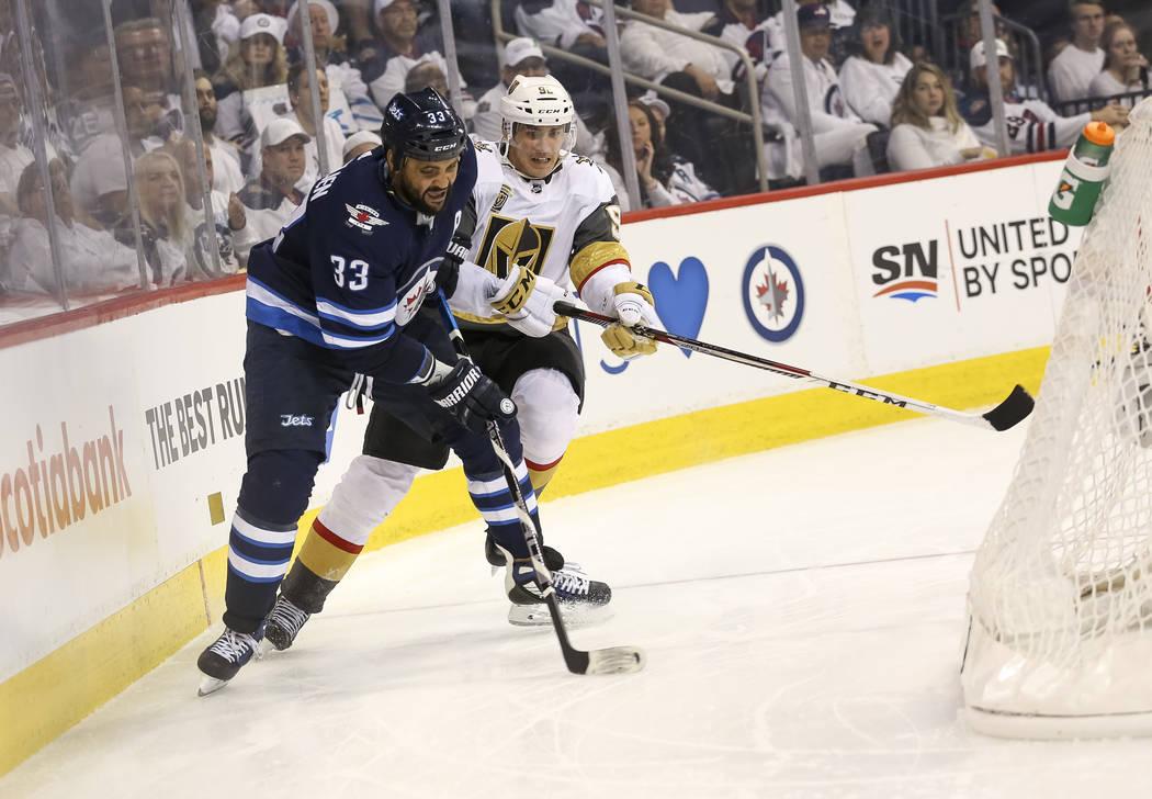 El defensor de los Jets de Winnipeg: Dustin Byfuglien (33), mantiene alejado al alero izquierdo de Vegas Golden Knights: Tomas Nosek (92) durante el segundo período en el Juego 2 de una serie de ...