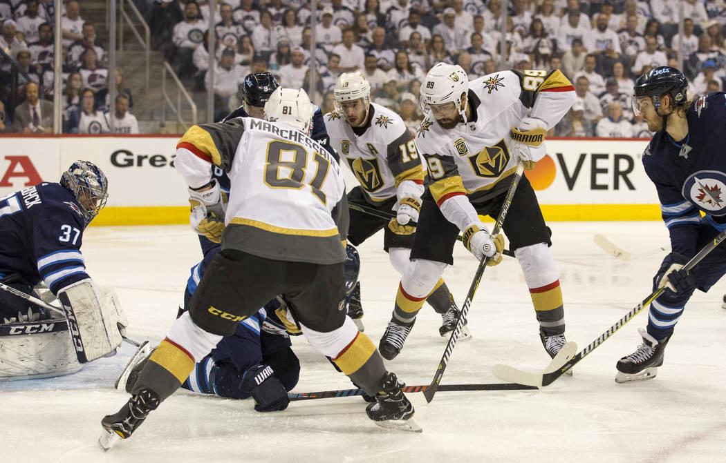 El centro Vegas Golden Knights: Jonathan Marchessault (81), Reilly Smith (19) y Alex Tuch (89) buscan el rebote contra los Jets de Winnipeg durante el segundo período en el Juego 2 de una serie d ...