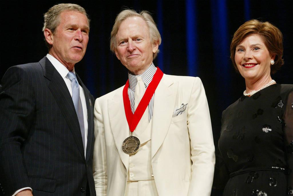 ARCHIVO - En esta foto de archivo del 22 de abril de 2002, el presidente Bush, izquierda, posa con el autor Tom Wolfe, en el centro, y la primera dama Laura Bush durante la ceremonia de Premios Na ...