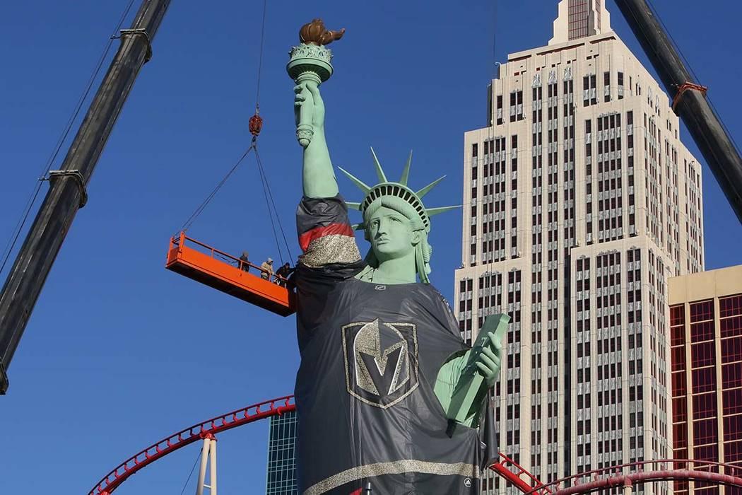 Trabajadores instalan una camiseta de los Vegas Golden Knights en la Estatua de la Libertad en el New York New York, el viernes 13 de abril de 2018, en Las Vegas. Bizuayehu Tesfaye / Las Vegas Rev ...