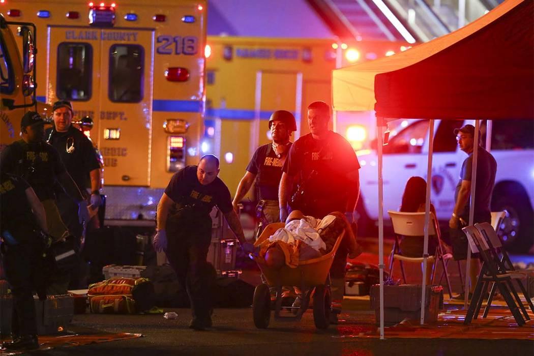 Una persona herida es ingresada en una carretilla mientras la policía de Las Vegas responde durante una sesión de disparos activos en el Strip de Las Vegas el domingo 1 de octubre de 2017. Chase ...