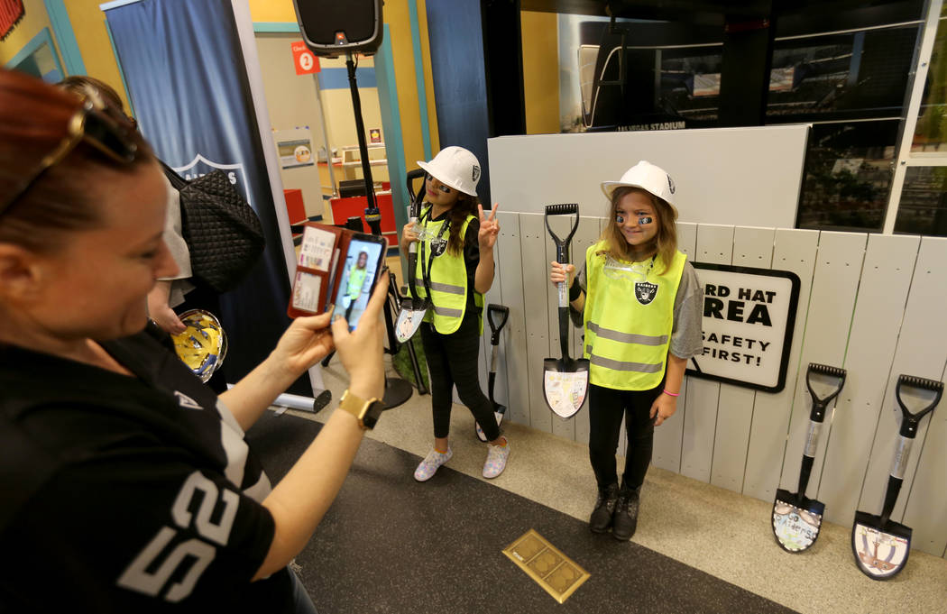 Lillian Allison, de ocho años, derecha, posa con su pala ganadora para su madre Katie Minor en la exhibición de la Zona de Construcción de Raiders Kids Construction en el DISCOVERY Children's M ...