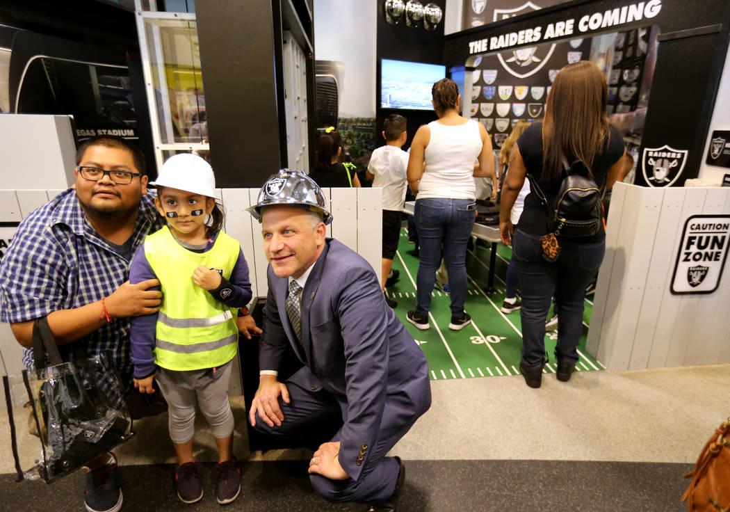Marc Badain, el presidente de los Raiders, derecha, posa con Wendy Carranco, de 5 años, y su padre Omar Gervacio durante la inauguración de la exhibición de la Zona de Construcción de Raiders ...