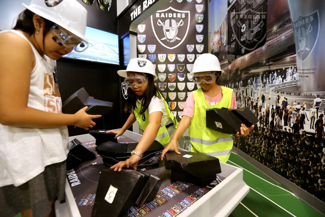 Kelly Galicia, 8, desde la izquierda, Ashley Santos, 9, y Jacqueline Romero, 8, construyen el estadio en la inauguración de la exhibición de la Zona de Construcción Infantil Raiders en el DISCO ...