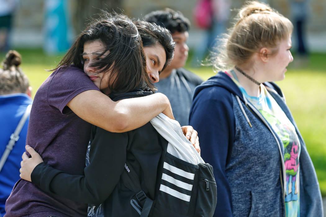 La estudiante de primer año de Santa Fe High School, Caitlyn Girouard, en el centro, abraza a su amiga fuera del Álamo Gym donde los estudiantes y padres esperan reunirse después de un tiroteo ...