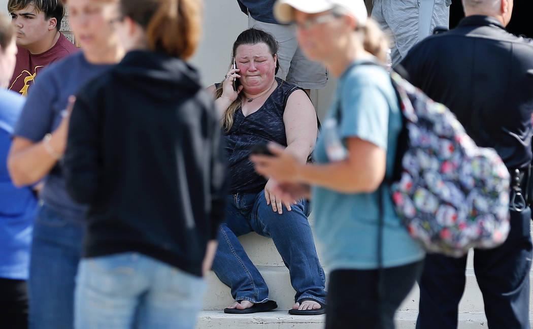 Una mujer reacciona mientras hace una llamada fuera del Álamo Gym donde los padres esperan para reunirse con sus hijos después de un tiroteo en Santa Fe High School en Santa Fe, Texas, el vierne ...