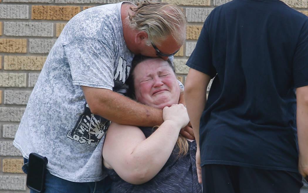 Un hombre abraza a una mujer afuera del gimnasio Alamo donde los padres esperan para reunirse con sus hijos después de un tiroteo en Santa Fe High School en Santa Fe, Texas, el viernes 18 de mayo ...