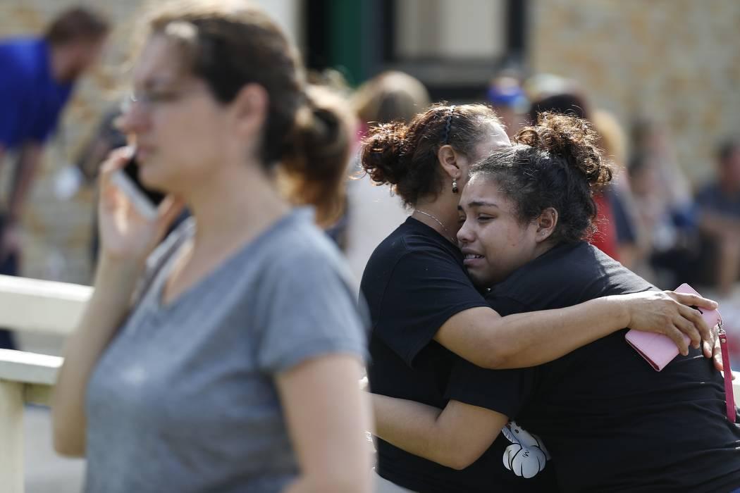 La estudiante de secundaria Santa Fe, Guadalupe Sánchez, de 16 años, llora en los brazos de su madre, Elida Sánchez, después de reunirse con ella en un punto de encuentro en el gimnasio Álamo ...