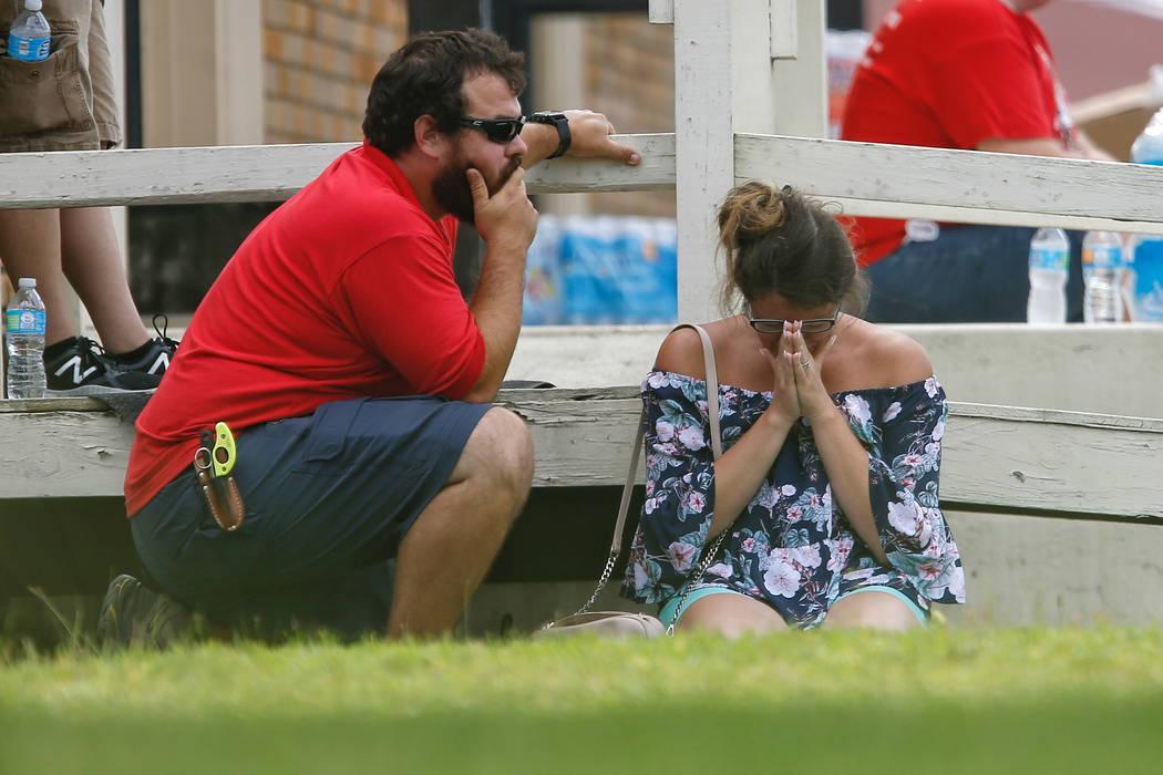 Una mujer reza en el césped afuera del gimnasio Alamo donde los padres esperan para reunirse con sus hijos después de un tiroteo en la escuela secundaria Santa Fe el viernes 18 de mayo de 2018 e ...
