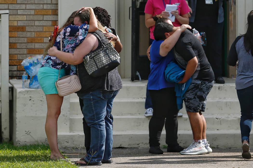La gente se abra en las afueras del gimnasio Álamo, donde los estudiantes y los padres esperan para reunirse después de un tiroteo en la escuela secundaria Santa Fe el viernes 18 de mayo de 2018 ...