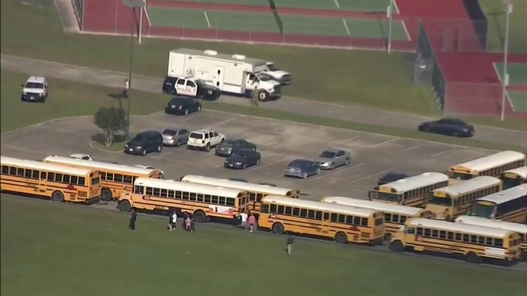 En esta imagen tomada del video, los oficiales encargados de hacer cumplir la ley responden a una escuela secundaria cerca de Houston después de que se reportó un tirador activo en el campus, el ...