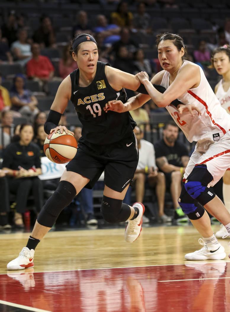 La centro de las Aces de Las Vegas, Ji-Su Park (19), conduce el balón contra la china, Jiacen Liu (12), durante un partido de pretemporada de baloncesto en el Mandalay Bay Events Center en Las Ve ...