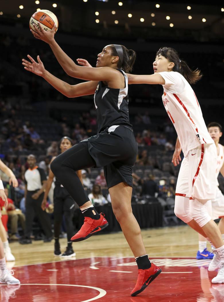 La centro, Asaja Wilson de Las Vegas (22), sube para superar a Zhengi Pan de China (17) durante un partido de pretemporada de baloncesto en el Mandalay Bay Events Center en Las Vegas el domingo 6 ...