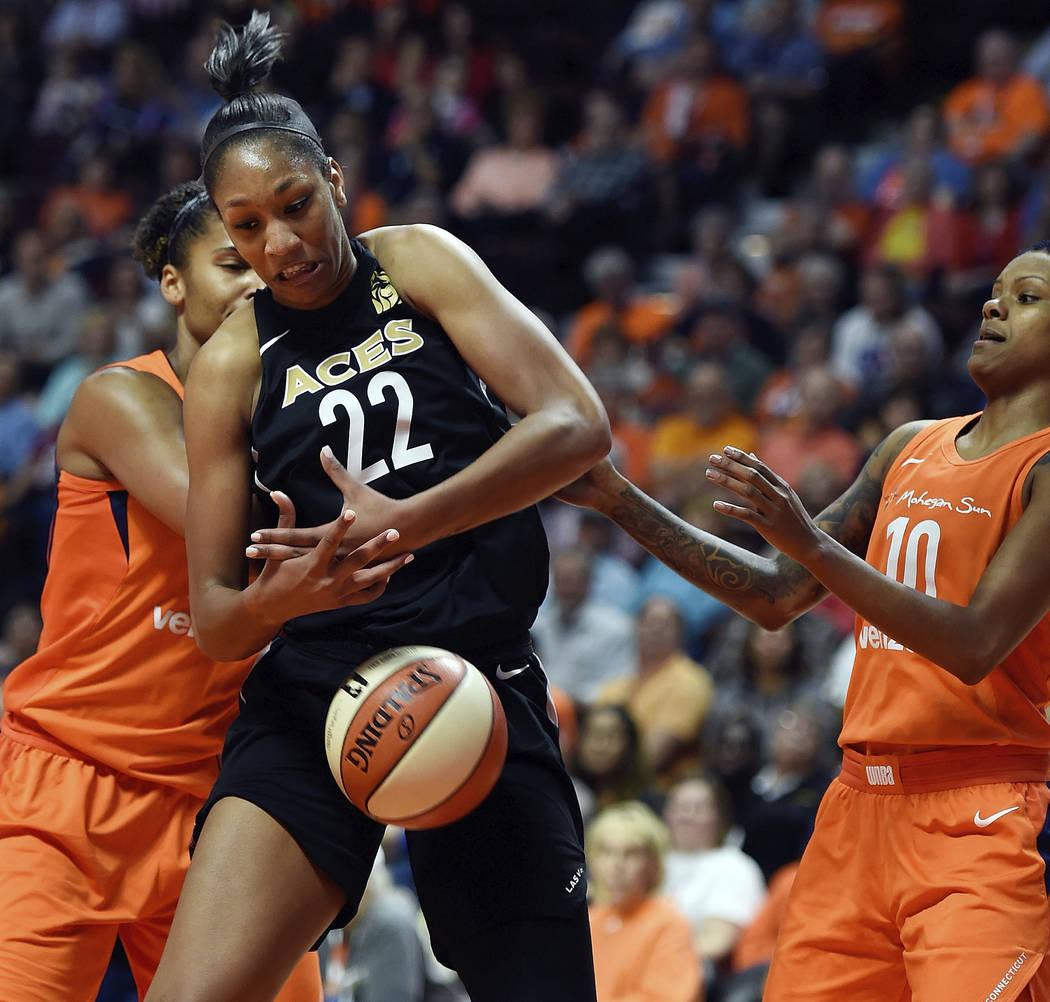 La alera de Las Vegas: A'ja Wilson (22), lucha contra la alera de Connecticut, Alyssa Thomas, izquierda, y la guardia Courtney Williams para un rebote en la primera mitad de la acción de la WNBA ...