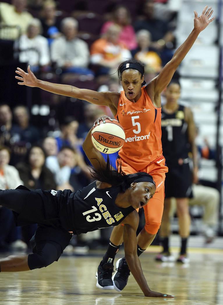 La guardia de las Aces de Las Vegas: Raigyne Louis (13), cae al suelo cuando la guardia del Connecticut Sun: Jasmine Thomas (5), se defiende en la segunda mitad de un partido de la WNBA el domingo ...