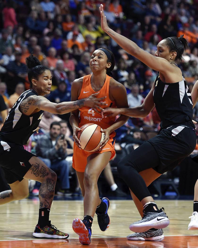 La guardia del Connecticut Sun: Lexie Brown, centro, recibe una falta de la alera de Las Vegas: Tamara Young, izquierda, mientras A'ja Wilson, a la derecha, ayuda en la defensa en la segunda mitad ...