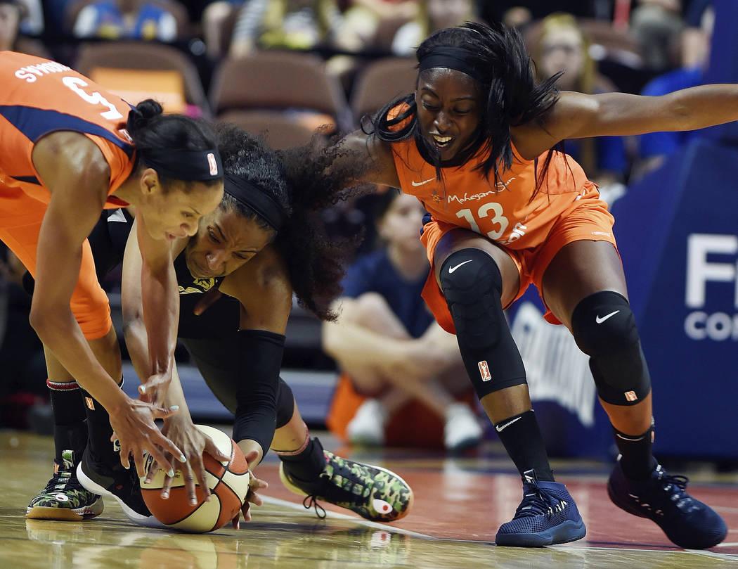 La guardia del Connecticut Sun: Jasmine Thomas, izquierda y la delantera: Chiney Ogwumike, derecha, lucha contra la centro de Las Vegas Aces: Kelsey Bone, por un balón suelto en la primera mitad ...