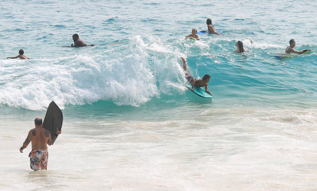 Los internos del cuerpo atrapan olas en Magic Sands Beach Park al sur de Kona, Hawai, el lunes 21 de mayo de 2018. Aunque el área afectada de las erupciones en curso es pequeña, algunos hoteles ...