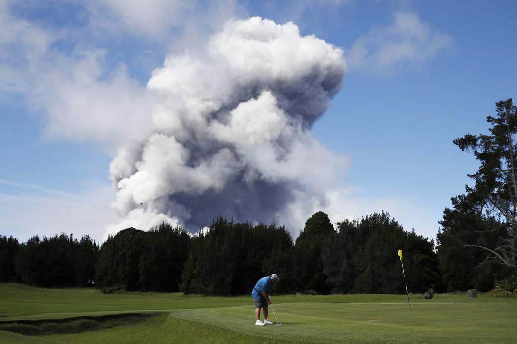 Doug Ralston juega al golf en Volcano, Hawai, mientras una enorme nube de ceniza se eleva desde la cima del volcán Kiluaea el lunes 21 de mayo de 2018. Kilauea ha quemado unas 40 estructuras, inc ...