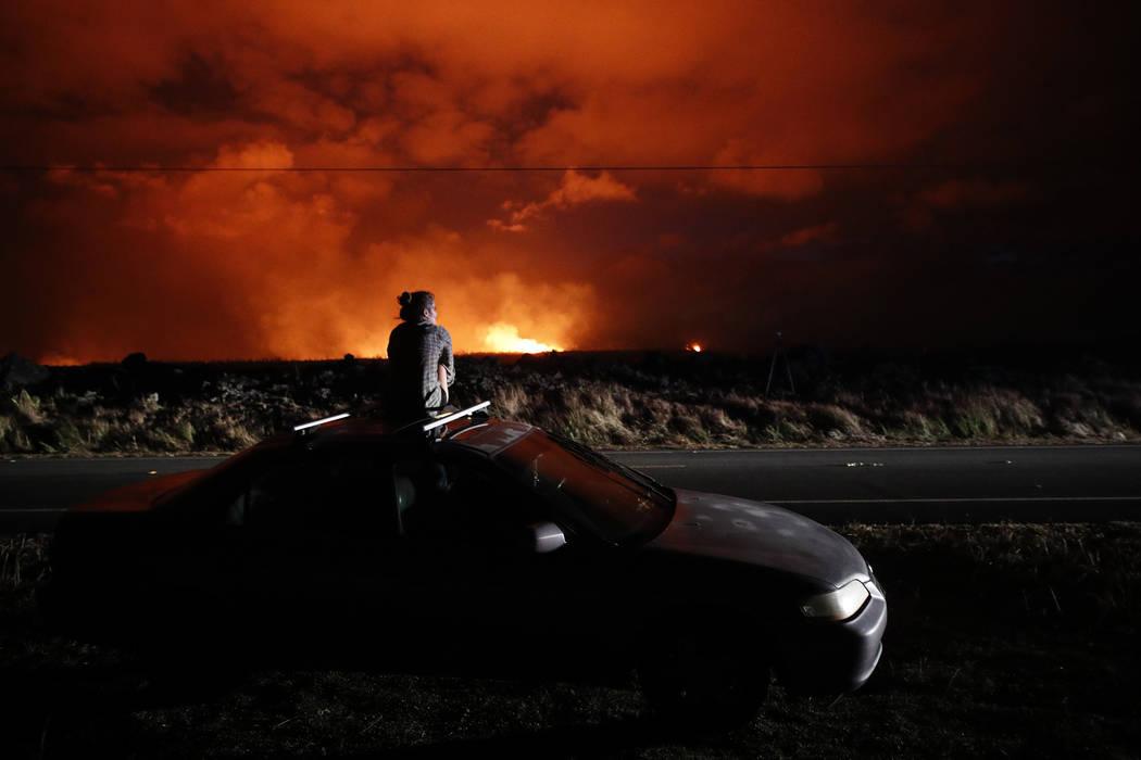 ARCHIVO - En esta foto de archivo del 19 de mayo de 2018, Brittany Kimball observa cómo la lava sale desde una fisura cerca de Pahoa, Hawaii. Plumas blancas de ácido y fragmentos de vidrio extre ...