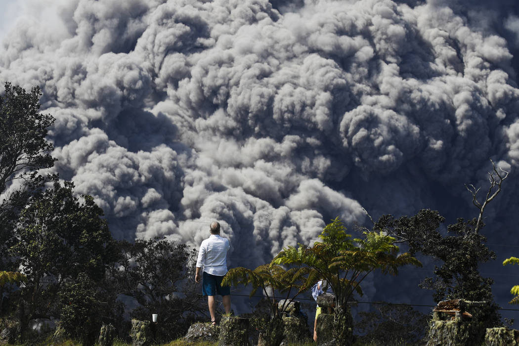 Jack Jones, visitando desde Madison, Wisconsin, toma fotos en un club de campo en Volcano, Hawai, mientras una gran nube de ceniza se eleva desde la cima del volcán Kiluaea el lunes 21 de mayo de ...