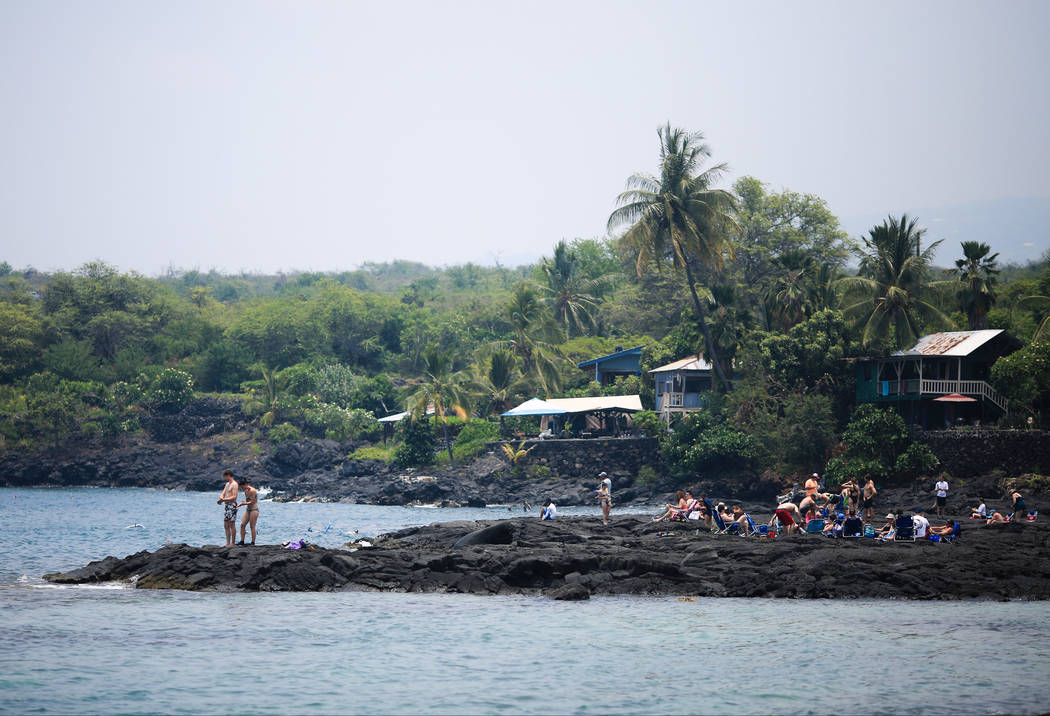 Los bañistas disfrutan de un día en Honaunau Beach en Hawaii, el lunes 21 de mayo de 2018. Aunque el área afectada de las erupciones en curso es pequeña, algunos hoteles han tenido cancelacion ...