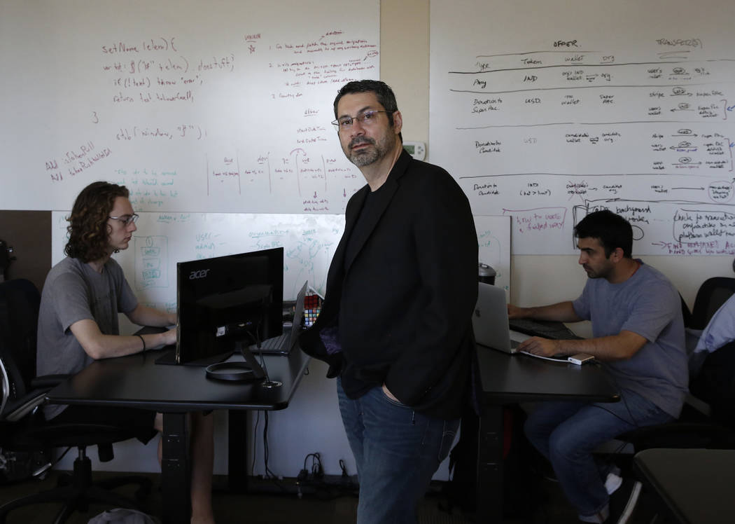 Rick Duggan, CEO de Concierge Software Design, posa para la foto como Triston Jones, izquierda, y Kandarp Dave, ambos ingenieros senior de software, trabajan en su proyecto en su oficina de Las Ve ...