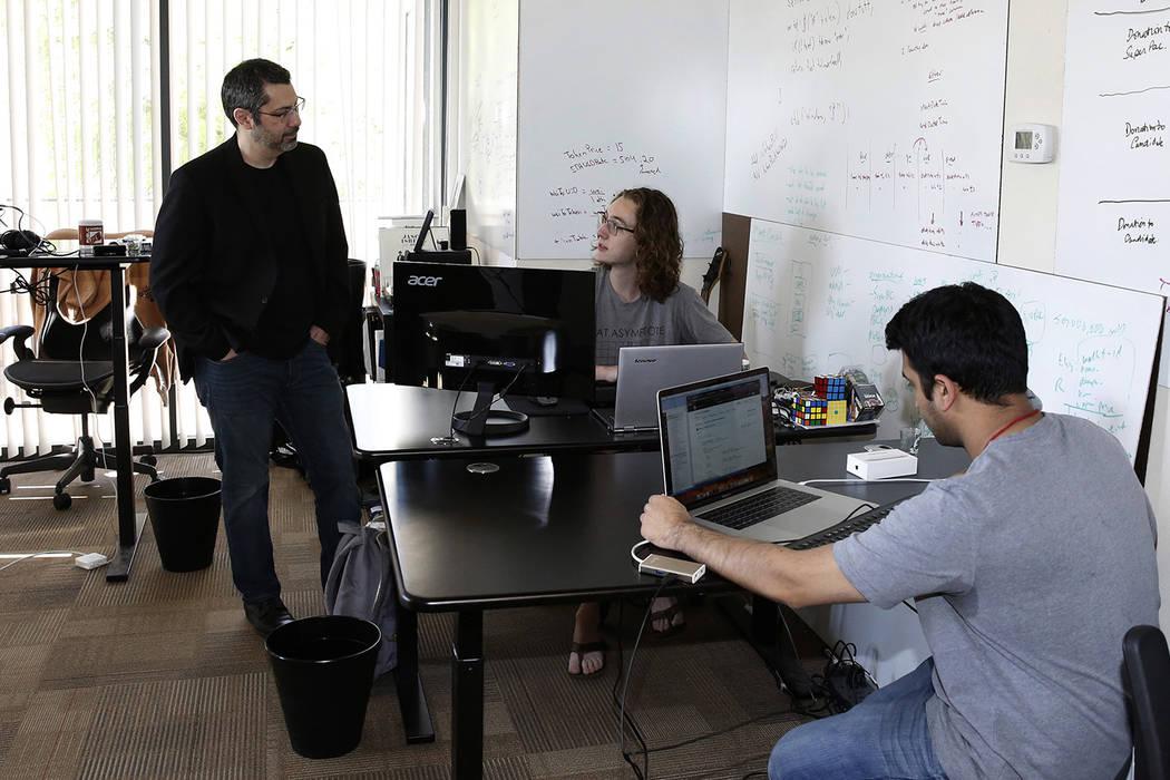 Rick Duggan, CEO de Concierge Software Design, conversa con Triston Jones, ingeniero senior de software, mientras Kandarp Dave, a la derecha, ingeniero senior de software, trabaja en su proyecto e ...