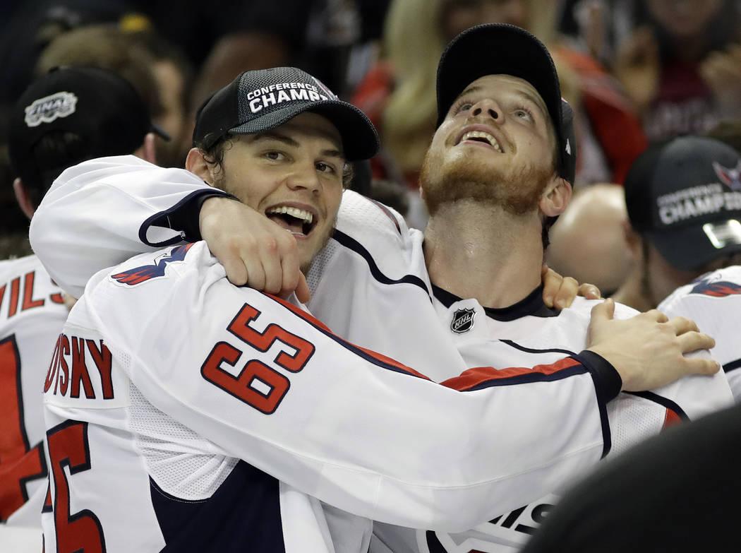 El ala izquierda de los Washington Capitals, André Burakovsky (65) y el defensa John Carlson celebran después de que los Capitals derrotaron al Tampa Bay Lightning 4 a 0 durante el Juego 7 de la ...