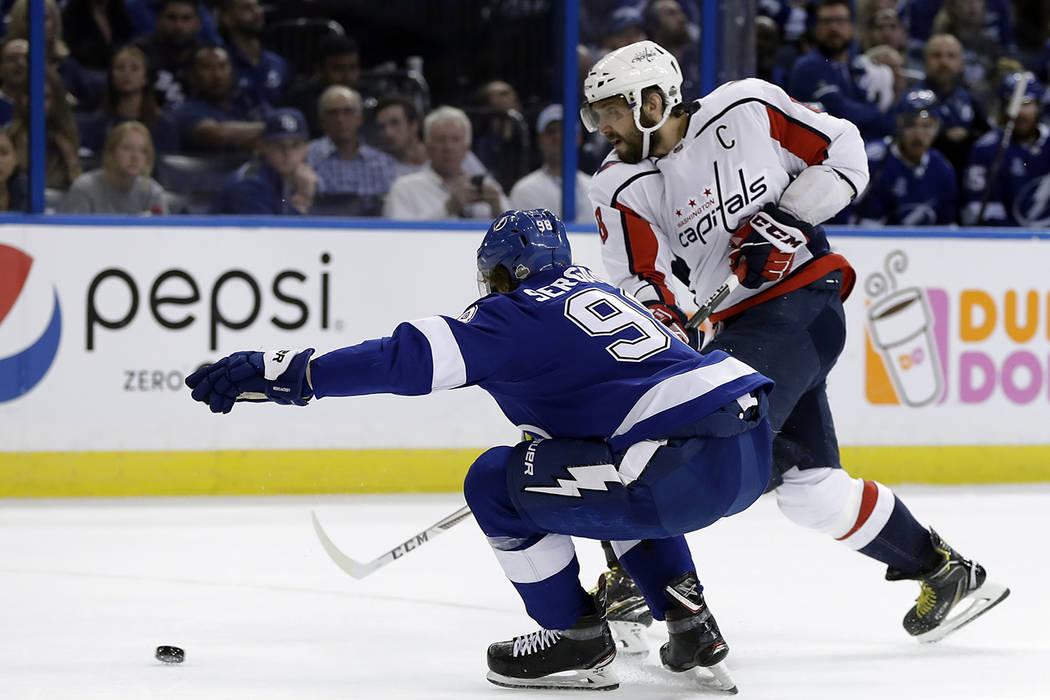 El ala izquierda de los Washington Capitals, Alex Ovechkin, adelanta el disco al defensor de Tampa Bay Lightning, Mikhail Sergachev, durante el primer periodo del séptimo juego de la serie de pla ...