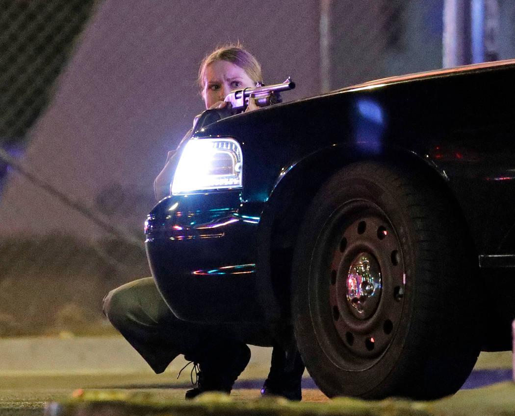 Un agente de policía se cubre detrás de un vehículo policial durante el tiroteo masivo cerca de Mandalay Bay en Las Vegas Strip el 1 de octubre de 2017. (John Locher / AP)
