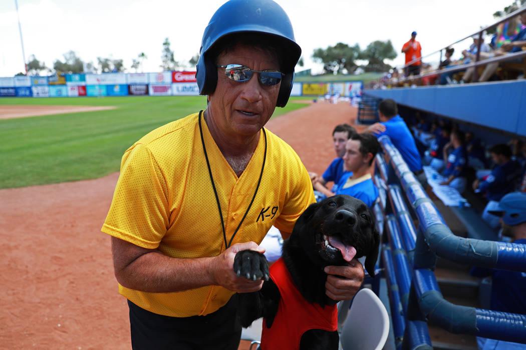 Fred Hassen, fundador del entrenamiento de perros Sit Means Sit, posa para una fotografía con el perro de los bates Finn de las Vegas 51s en el Cashman Field de Las Vegas el domingo 13 de mayo de ...