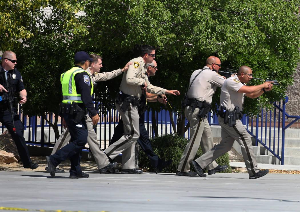Los oficiales de policía de Las Vegas apuntan sus armas cuando se acercan a Shadow Ridge High School donde el miércoles 30 de mayo de 2018, en Las Vegas, se realizó un simulacro de tiroteo masi ...