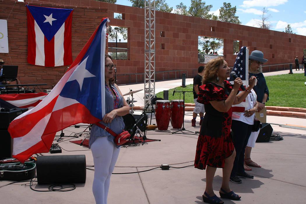 Ana Acevedo sostiene la bandera de Puerto Rico y Mónica Ortiz canta el himno de la isla, el 27 de mayo del 2018, en el anfiteatro del gobierno del Condado Clark. Foto Valdemar González / El Tiem ...