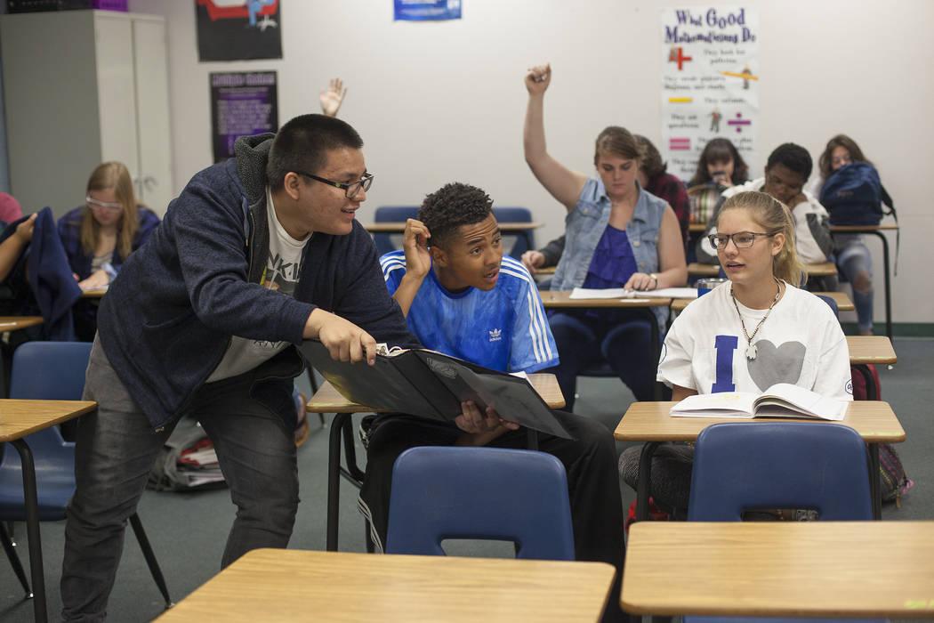 Carlos Hernández-Muñoz señala la respuesta a D'Andre Burnett y Marykate Springer mientras un grupo de estudiantes encabeza una presentación en clase de matemáticas en Shadow Ridge High School ...