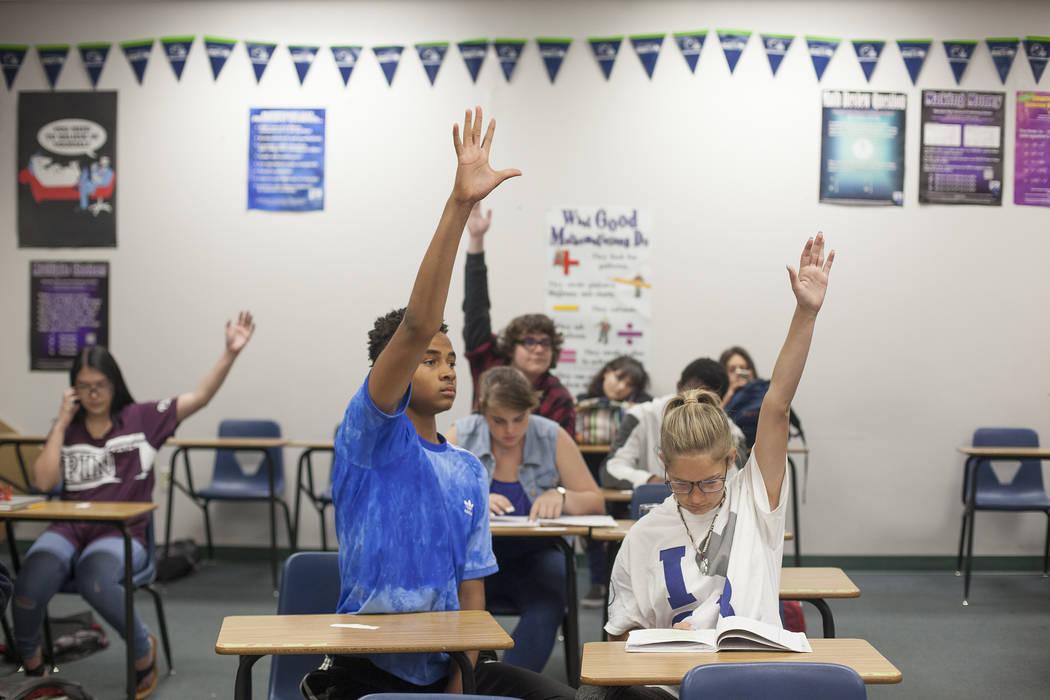 D'Andre Burnett, izquierda, levanta la mano para responder una pregunta junto a Marykate Springer en la clase de matemáticas en Shadow Ridge High School en Las Vegas, miércoles 16 de mayo de 201 ...