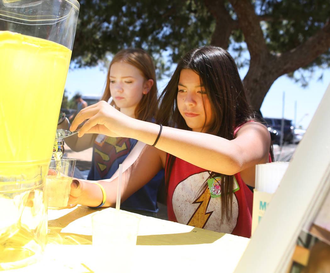 Mallory Poushay, de 13, izquierda, y Alyciana Rivas, de 13, reparten limonada durante la recaudación de fondos de Alex's Lemonade Stand Foundation para la investigación de cáncer infantil en Su ...