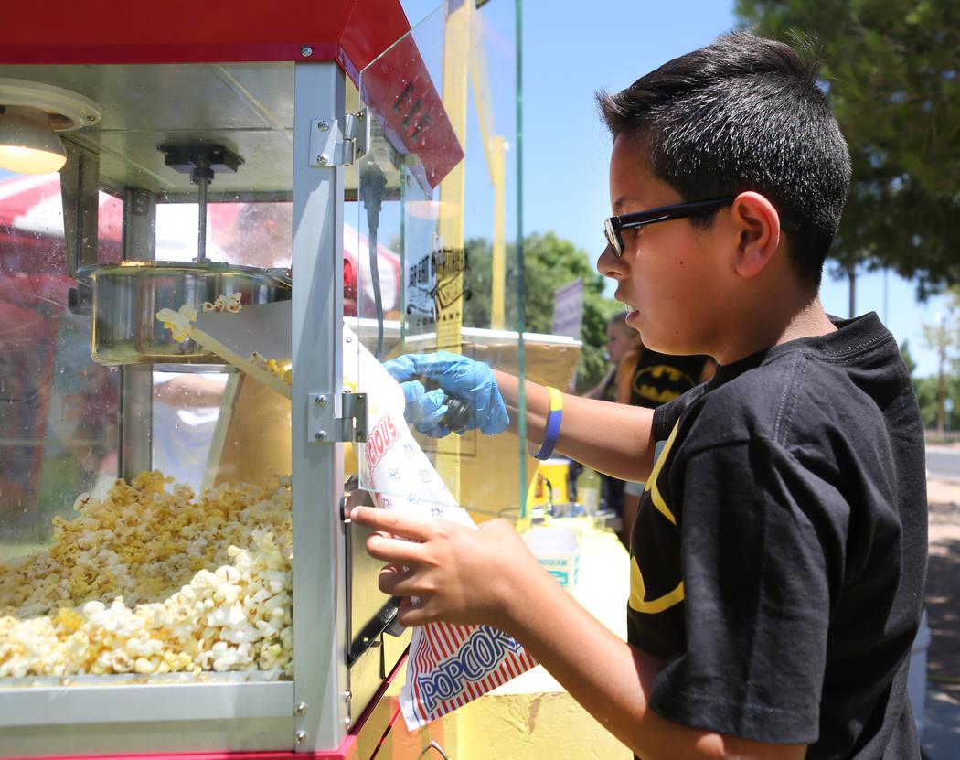 Tommy Ramos, de 11 años, prepara palomitas de maíz durante una recaudación de fondos para Alex's Lemonade Stand Foundation, una fundación nacional contra el cáncer infantil, en Sunset Park en ...